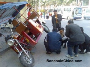chinese-men-helping-repair-three-wheeled-taxi-in-china